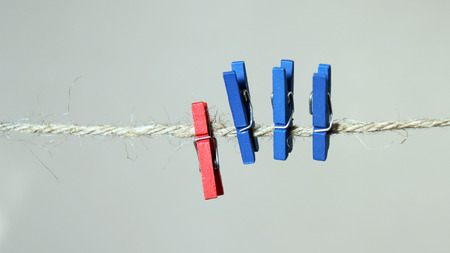 Three blue laundry clips and a red laundry clip on a rope.