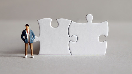 Two puzzles and a miniature man standing up.