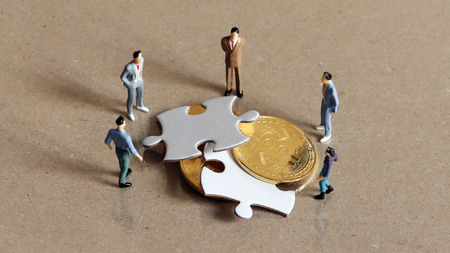 Five miniature people staring down two pieces of the puzzle and bitcoin. Stockfoto