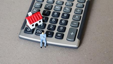 A miniature man sitting calculator. A miniature house and miniature people.