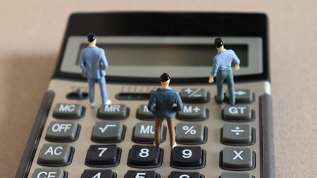 Three miniature men standing on the calculator.