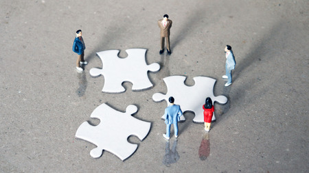 Five miniature people staring down three pieces of the puzzle.
