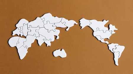 A world map puzzle with a brown background Stock Photo