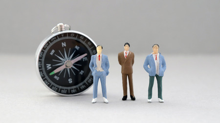 Three miniature men standing in front of the compass.