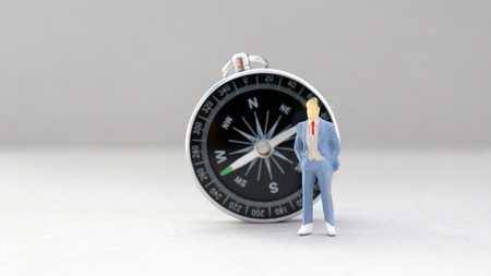 A miniature man standing in front of the compass.