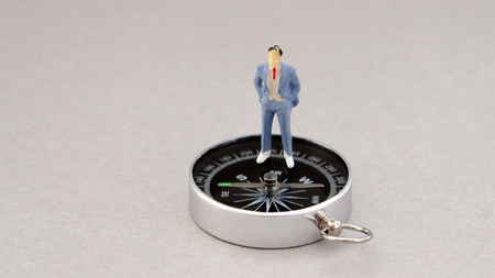 A miniature man standing on a compass. Stock Photo