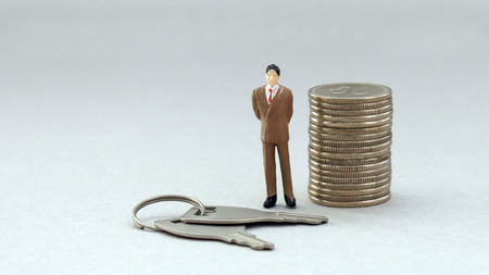 Middle-aged man miniature with a bunch of keys and coins. Stock Photo