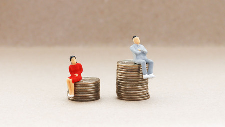 Gender discrimination concept. A miniature woman and a man sitting on a pile of coins.