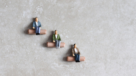 Miniature people sitting at different heights. Concept of job discrimination.