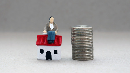 Concept of retirement planning. A miniature man sitting on a miniaturization house is a pile of coins.
