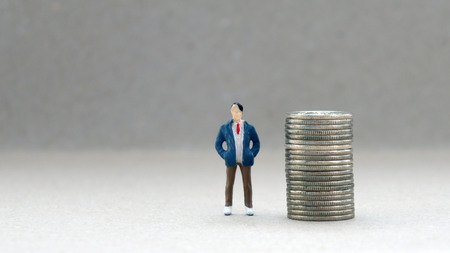A miniature man standing next to a pile of coins.