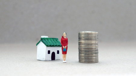 A miniature woman standing between a pile of coins and a miniature house.