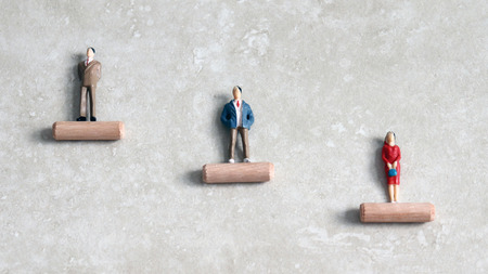 Miniature men and women standing at different heights.