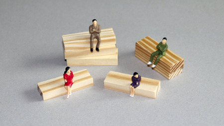 Two miniature men and two miniature women sitting on blocks of different heights. Stock Photo