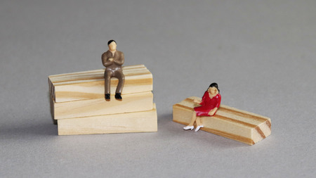 A miniature man and a miniature woman sitting on a tree at different heights.