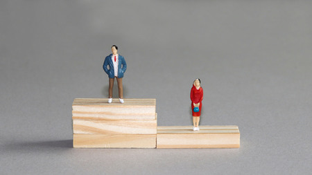 A miniature man and a woman standing on different wooden blocks.