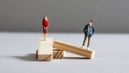 A miniature man and a miniature woman standing on a twisted block of wood. Stock Photo