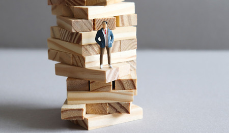 A miniature man standing in the middle of a pile of wooden blocks.