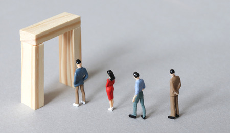 Miniature people lined up to the narrow doors. Standard-Bild