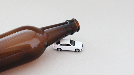 The concept of drunk driving. Bottle and miniature automobile.
