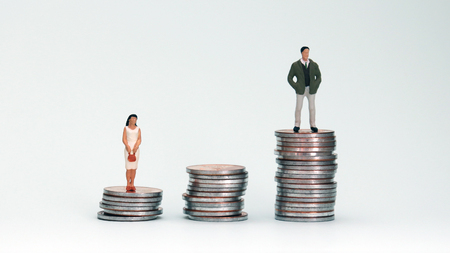 A miniature woman standing in a pile of low coins and a miniature man standing in a pile of tall coins.
