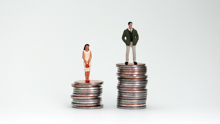 A miniature man and woman standing on a pile of coins at different heights.