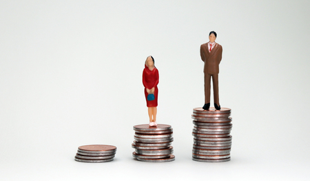 Gender wage difference concept. Three piles of different heights coins and miniature people.