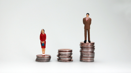 Gender wage difference concept. A miniature woman standing on a pile of tall coins. Stock Photo