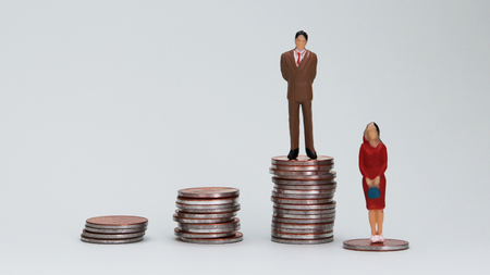 Gender wage difference concept. A miniature man and a woman standing on top of a pile of coins. Stock Photo