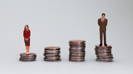 Gender wage difference concept. The miniature men and women are standing on the coin tower.