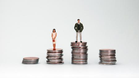 コインとミニチュアの人々の4つの山。男女の賃金格差という概念。