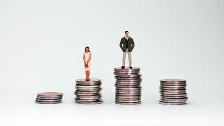 Four piles of coins and miniature people. The concept of wage disparity between men and women.