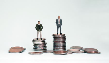 Two miniature men on top of another pile of coins. Stockfoto