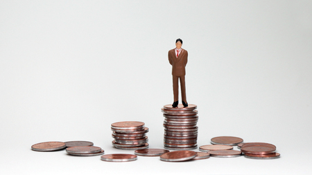 A miniature man standing on top of a pile of coins. A successful male concept.