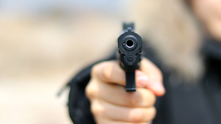 Woman pointing a gun at the target on soft background.