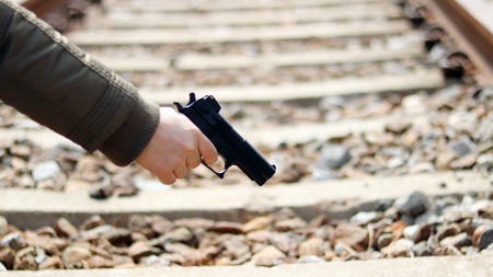 A hand of woman with a gun.