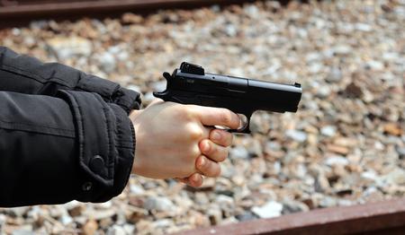 A womans hand pointing a gun.