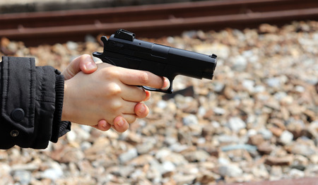 A womans hand pointing a gun. Concept of risk of possessing an illegal weapon. Stock Photo