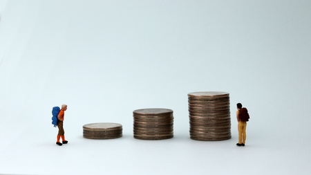 Three piles of coins and two miniature people.