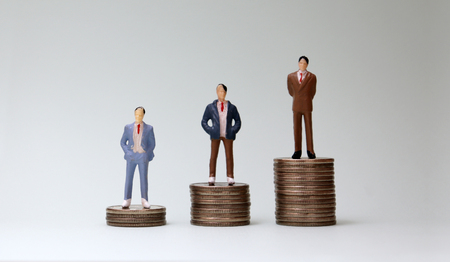 Miniature men standing on top of three coins of different heights. Stock Photo