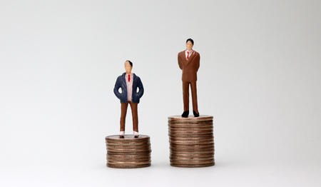 Two miniature men standing on top of two coins of different heights.