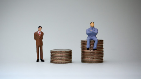 A miniature man sitting in a pile of coins and a miniature man standing behind a pile of coins.