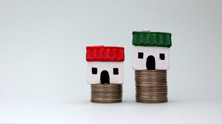 Two miniature houses on top of a stack of coins of different heights.