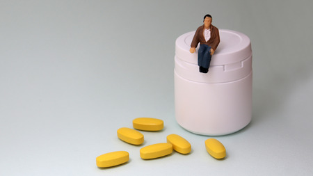 A miniature man sitting on a medicine bottle. Stock Photo