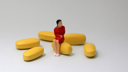 A miniature woman is sitting on a pills beside several yellow pills. Stock Photo