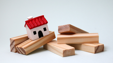 A miniature house and wooden blocks.