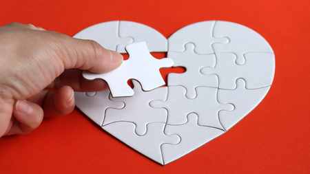 A hand holding a puzzle of a heart puzzle.