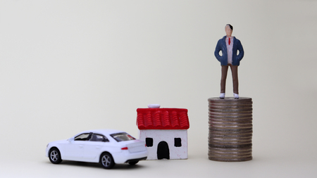 A miniature man standing on a pile of coins. A miniature house and a miniature car. Фото со стока