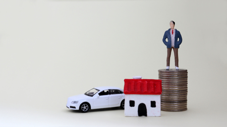 A miniature man standing on a pile of coins.