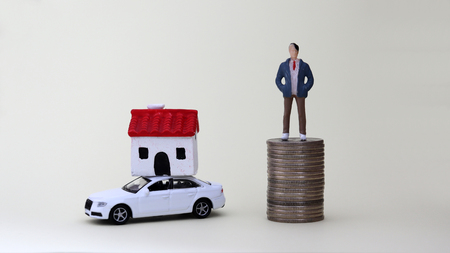 A miniature man standing on a pile of coins. A miniature house on a miniature car. Фото со стока